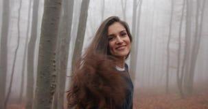 De herfst vibes, draagt de mistige bos Aantrekkelijke donkerbruine vrouw met lang haar toevallige uitrusting en loopt over het bo stock footage
