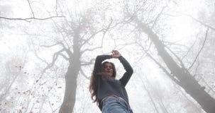 De herfst vibes, draagt de mistige bos Aantrekkelijke donkerbruine vrouw met lang haar toevallige uitrusting en loopt over het bo stock video