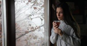 De herfst vibes, vakantie in de bergen Het charmeren van donkerbruine vrouw in grijze sweater drinkt thee die zich door het venst stock footage