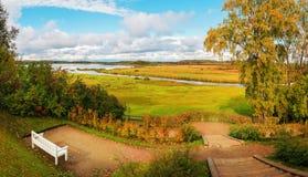 De herfstaard - de herfstlandschap van rivier en de herfstbomen in bewolkt weer Stock Foto's