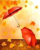 De herfstachtergrond met de herfstbladeren en oranje paraplu's Stock Foto