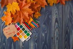 De herfstachtergrond met kleurenbladeren op blauwe raad Stock Afbeeldingen