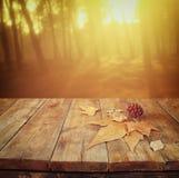 De herfstachtergrond van gevallen bladeren over houten lijst en bos backgrond met lensgloed en zonsondergang Stock Foto's