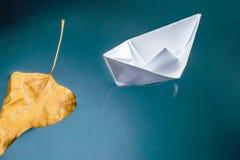 De herfstblad en een document boot op de waterspiegel Royalty-vrije Stock Afbeelding
