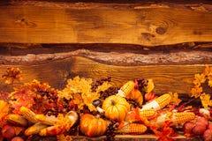 De herfstbladeren, bessen en groenten bij donkere houten backgro Royalty-vrije Stock Fotografie
