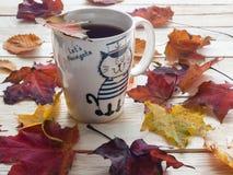 De herfstbladeren en kop thee Stock Foto