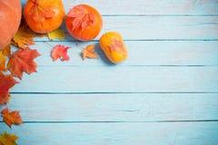 De herfstbladeren en pompoenen op houten achtergrond Royalty-vrije Stock Afbeeldingen