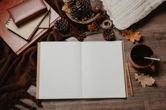 De herfstbladeren, notitieboekje en mok op rustieke houten lijst, comfortabel de herfststilleven, het concept van de de herfstste Stock Afbeelding