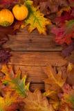 De herfstbladeren op de bruine houten lijst Stock Afbeeldingen