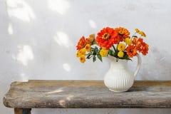 De herfstbloemen in waterkruik op houten bank stock afbeeldingen