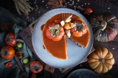 De de herfstcake met dadelpruim en karamel met een pompoen en een meisje in Bourgondië kleden zich op een zwarte achtergrond, Atm stock afbeeldingen