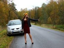 De de herfstdag op splitste de auto en het meisje in een kleding met een hoed haalt een andere te helpen auto royalty-vrije stock foto's
