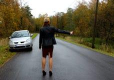 De de herfstdag op splitste de auto en het meisje in een kleding met een hoed haalt een andere te helpen auto stock foto's