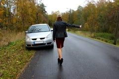 De de herfstdag op splitste de auto en het meisje in een kleding met een hoed haalt een andere te helpen auto royalty-vrije stock foto