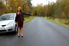 De de herfstdag op splitste de auto en het meisje in een kleding met een hoed haalt een andere te helpen auto royalty-vrije stock afbeelding