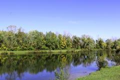 De herfstgebladerte die een kalme blauwe vijver overdenken stock foto