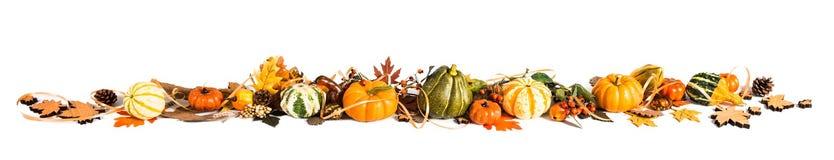 De herfstgrens van bladeren en pompoenen wordt gemaakt die Stock Foto