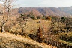 De herfstlandschap die een oud traditioneel die plattelandshuisje vertegenwoordigen, door bomen en bergen wordt omringd stock fotografie