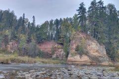 De herfstlandschap en rode steenklip van Amata-rivier, Letland, Europa royalty-vrije stock foto