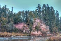De herfstlandschap en rode steenklip van Amata-rivier, Letland, Europa royalty-vrije stock foto's