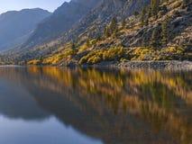 De herfstlandschap met duidelijk bergmeer en de gouden bezinning van de bomenspiegel royalty-vrije stock afbeelding