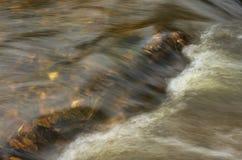 De herfstlandschap met een snelle stroom en gevallen bladeren stock afbeeldingen