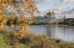 De herfstlandschap met esdoorntak en rivier stock fotografie