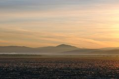 De herfstlandschap met schoongemaakt landbouwgebied tijdens spectaculaire gouden zonsopgang boven vlotte heuvels stock afbeeldingen