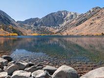 De herfstlandschap met stenen voor het meer en de bergen stock foto's
