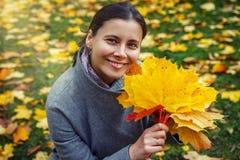 De herfstmeisje met kleurrijke in hand bladeren Close-up in openlucht portret van jonge donkerbruine Kaukasische vrouw die grijze Stock Foto's