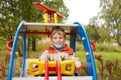 In de herfstmiddag, speelt de jongen op speelplaats Royalty-vrije Stock Foto's