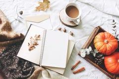 De herfstontbijt in bedsamenstelling Kaart, notitieboekjemodel Kop van koffie, eucalyptusbladeren, pompoenen op houten dienblad stock fotografie
