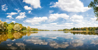 De herfstpark, bomen en blauwe die hemel in water wordt weerspiegeld Royalty-vrije Stock Fotografie