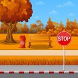 De herfstpark met eindeteken op stadskant van de weg en bank Stock Foto