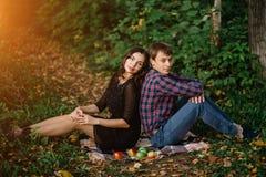 De herfstpicknick, een jong mooi paar in het hout Een man en een vrouwenzitting op een deken royalty-vrije stock fotografie