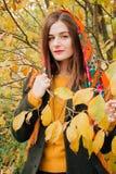 De herfstportret, jong mooi meisje met lang haar in Russische sjaal en geel gebladerte royalty-vrije stock fotografie