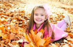 De herfstportret van aanbiddelijk meisje met esdoornbladeren Stock Afbeeldingen