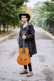 De herfstportret van de jonge kerel met gitaar stock foto