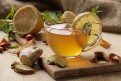 De herfstsamenstelling met hete thee met gember en citroen op een natuurlijke houten lijst stock foto