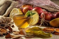 De herfstsamenstelling met hete thee, vruchten en gele bladeren op een natuurlijke houten lijst royalty-vrije stock foto's
