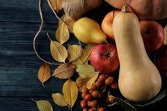 De herfstsamenstelling met pompoen en de herfstvruchten met appelen en peren en gele bladeren op een donkerblauwe lijst royalty-vrije stock foto's
