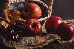 De herfstsamenstelling met verse rode appelen en kaneel in een houten mand op rustieke houten achtergrond Rode appelen en kaneel Stock Foto