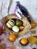De de herfstsamenstelling van pompoenen, peren, decor, gaat op een lichte achtergrond van geweven document weg royalty-vrije stock afbeeldingen