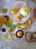De de herfstsamenstelling van pompoenen, peren, decor, gaat op een lichte achtergrond van geweven document weg royalty-vrije stock fotografie