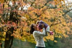 De herfstscène van moeder die jong babymeisje in openlucht kussen royalty-vrije stock afbeeldingen