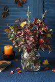 De herfststilleven - boeket van de herfstbladeren, kaars, blocnote voor het trekken op de donkere lijst De stemming van de herfst Stock Foto's