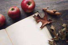 De herfststilleven met appelen, open boek en bladeren over rustieke houten achtergrond Royalty-vrije Stock Fotografie