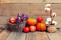 De herfststilleven met pompoenen, groenten en katoen op een hout stock afbeeldingen