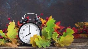 De herfsttijd - dalingsbladeren met klok stock footage