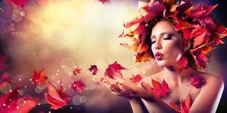 De herfstvrouw die rode bladeren blaast Stock Afbeelding